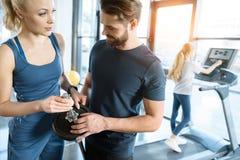 Человек и женщина стоя с штангой пока малая разминка девушки дальше на третбане на спортзале Стоковое Изображение RF