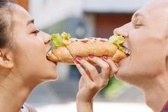 Человек и женщина сдерживая такую же горячую сосиску Стоковое фото RF