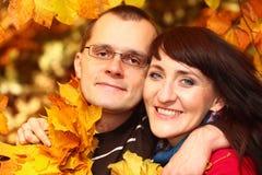 Человек и женщина с листьями осени в руках Стоковое Фото