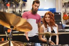 Человек и женщина с набором барабанчика на магазине музыки Стоковые Фотографии RF