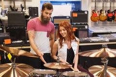 Человек и женщина с набором барабанчика на магазине музыки Стоковое фото RF