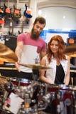 Человек и женщина с набором барабанчика на магазине музыки Стоковая Фотография