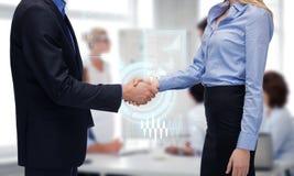Человек и женщина тряся их руки в офисе Стоковое фото RF