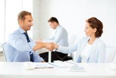 Человек и женщина тряся руки в офисе Стоковое Изображение