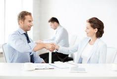 Человек и женщина тряся руки в офисе Стоковые Фото