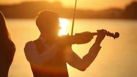 Человек и женщина дуэта скрипки играют скрипку на природе на заходе солнца на озере сток-видео