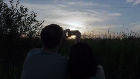 Человек и женщина фотографируют заход солнца на их телефоне видеоматериал