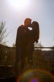Человек и женщина целуя на фоне заходящего солнца силуэт Стоковое Изображение RF
