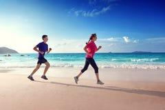 Человек и женщины бежать на тропическом пляже Стоковые Фото