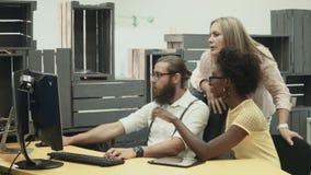 Человек и женщины обсуждая проект на компьютере видеоматериал