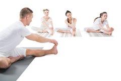 Человек и женщины практикуя йогу совместно на циновках йоги Стоковые Изображения