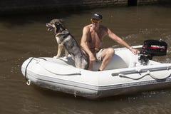 Человек и собака в моторизованной резиновой шлюпке на солнечный день в лете Стоковые Изображения RF