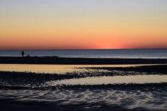 Человек и собака на пляже на восходе солнца Стоковые Изображения