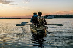 Человек и туристы женщины плавая в каное на заходе солнца на озере l Стоковые Фото