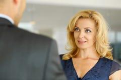 Человек и усмехаясь зрелая женщина говоря в офисе Стоковое Изображение