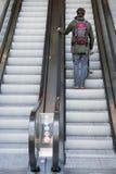 Человек идя вверх на эскалатор Стоковые Фото
