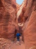 Человек идя вниз с узкого каньона стоковая фотография