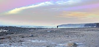 Человек идя на скалистый пляж Стоковая Фотография RF