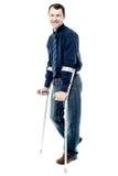 Человек идя при костыли изолированные на белизне стоковые фотографии rf