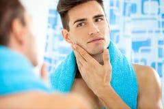 Человек касаясь его стороне после брить