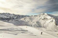 Человек катания на лыжах среди гор снега стоковое изображение rf