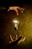 Человек контролирует электрическую лампочку Стоковая Фотография RF