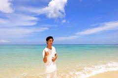 Человек который ослабляет на пляже Стоковое фото RF