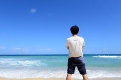 Человек который ослабляет на пляже Стоковая Фотография