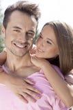 Человек красивой молодой женщины обнимая от заднего в парке Стоковая Фотография RF