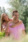 Человек красивой молодой женщины обнимая от заднего в парке Стоковые Изображения