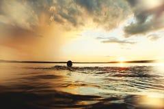 Человек купает в озере на заходе солнца красивейший заход солнца Стоковое Изображение RF