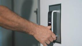 Человек кладет его палец на блок развертки отпечатка пальцев который конструирован для того чтобы войти дверь Современная техноло сток-видео