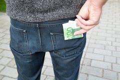 Человек кладет деньги в его карманн задней части Стоковые Изображения