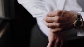 Человек кладет запонки для манжет на рукави белой рубашки Конец-вверх видеоматериал