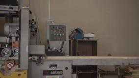 Человек кладет длинную деревянную доску на машину woodworking на мебели изготовления акции видеоматериалы