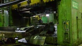 Человек кладет компонент под фабрику AutoVAZ машины прессы 30-ого сентября 2011 в Togliatti, Россию видеоматериал