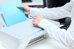 Человек кладет стог бумаги к принтеру Стоковые Фотографии RF