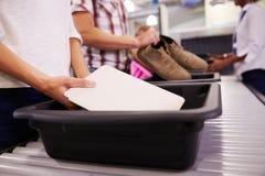 Человек кладет таблетку цифров в поднос для проверки службы безопасности аэропорта стоковое изображение rf