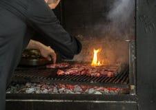 Человек кладет части свежего мяса на гриль Стоковые Изображения