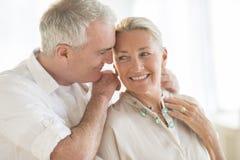 Человек кладя ожерелье вокруг шеи женщины дома Стоковые Фото