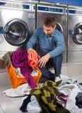 Человек кладя пакостные одежды в корзину на Laundromat стоковая фотография rf