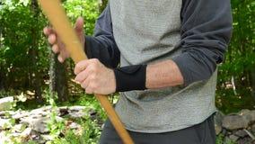 Человек массажируя запястье руки держа бейсбольную биту акции видеоматериалы