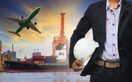 Человек менеджера держа шлем безопасности стоя против корабля и cont Стоковая Фотография RF