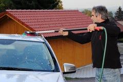 Человек моет его автомобиль Стоковые Фото