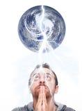 Человек моля и смотря вверх землю стоковое изображение rf