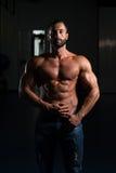 Человек мышцы представляя в спортзале Стоковые Фото