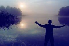 Человек наблюдая восход солнца над озером людской силуэт Стоковое Изображение RF