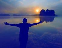Человек наблюдая восход солнца над озером людской силуэт Стоковая Фотография