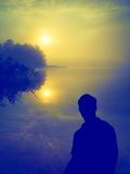 Человек наблюдая восход солнца над озером людской силуэт Стоковая Фотография RF