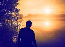 Человек наблюдая восход солнца над озером людской силуэт Стоковое Фото